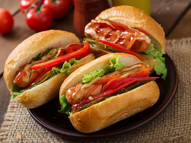 ホットドッグ-ピクルス、パプリカ、木製の背景にレタスのサンドイッチ