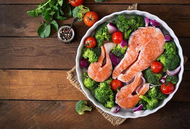 生サーモンステーキと素朴なスタイルの暗い木製の背景で調理するための野菜。上面図