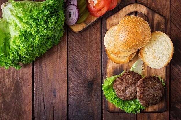 サンドイッチの材料-牛肉、漬物、トマト、木製の背景に赤玉ねぎのハンバーガーハンバーガー。上面図