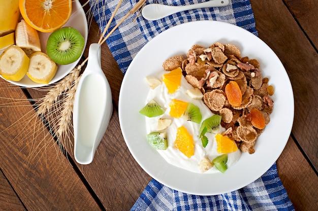 ミューズリーとテーブルの上の白いプレートにフルーツの健康的なデザート