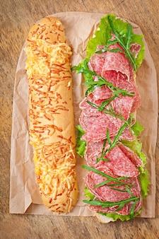 サラミ、レタス、トマト、ルッコラのサンドイッチ