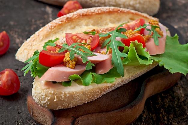 古い木製の表面にソーセージ、レタス、トマト、ルッコラのサンドイッチ