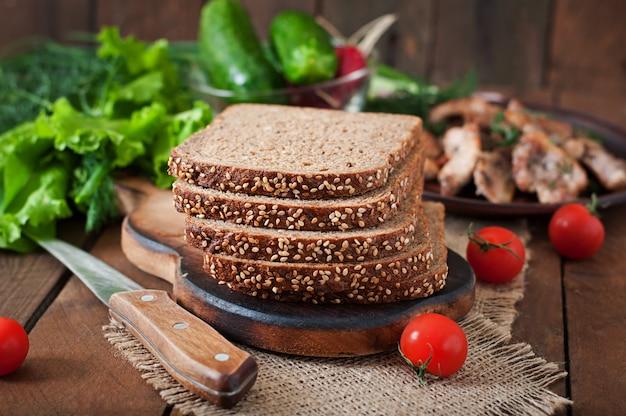 全粒ライ麦パン、ふすまと木製のテーブルの種