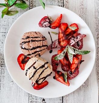 Мороженое с клубникой и шоколадом на белой тарелке