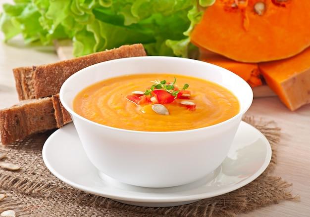 木製のテーブルの上にボウルにカボチャのスープのおいしいクリーム