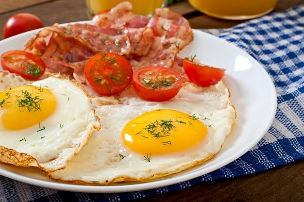 木製のテーブルで素朴なスタイルのトースト、卵、ベーコン、野菜のイングリッシュブレックファースト