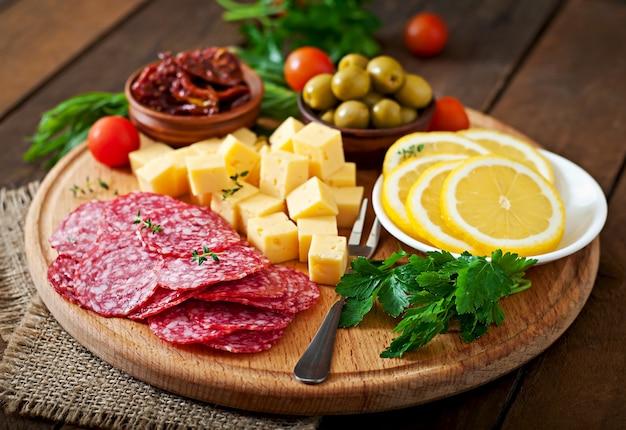 サラミと木製のテーブルの上のチーズの前菜ケータリングの盛り合わせ