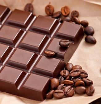 ベージュの紙の上にチョコレートとコーヒー豆