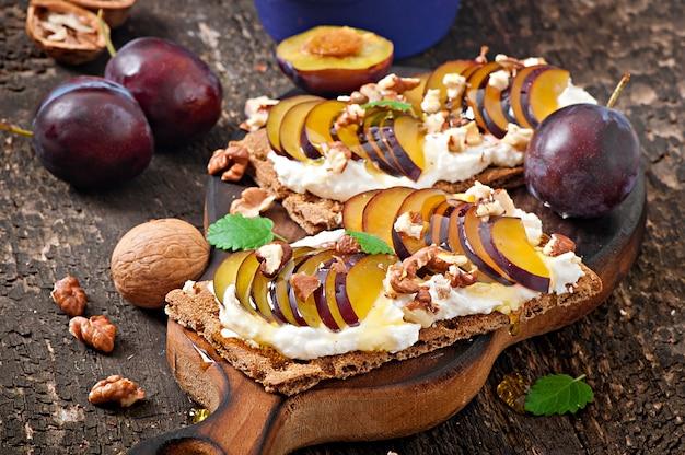 Сэндвичи с вегетарианской диетой хлебцы с творогом, сливами, орехами и медом на старых деревянных