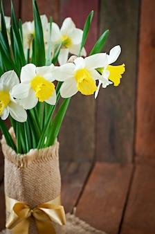 素朴な木製の黄色い水仙の花束をクローズアップ