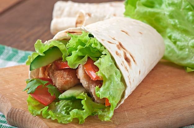Свежие тортилла обертывания с куриными наггетсами и овощами на тарелке