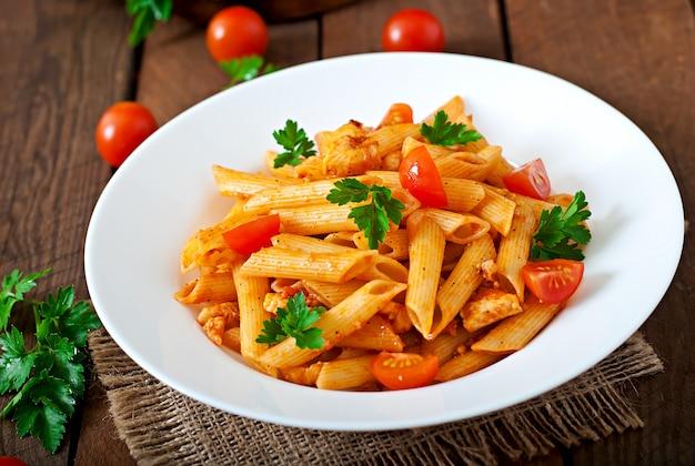 Паста пенне в томатном соусе с курицей и помидорами на деревянном столе
