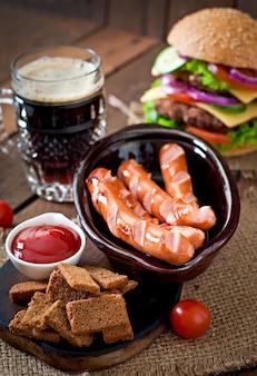 Жареные колбаски, крекеры и пиво на деревянном столе в деревенском стиле.