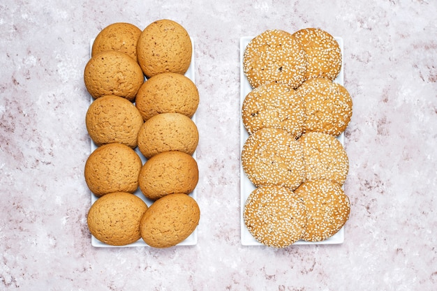 Комплект различных печений американского стиля на светлой конкретной предпосылке. песочное печенье с конфетти, кунжутом, арахисовым маслом, овсянкой и шоколадным печеньем.