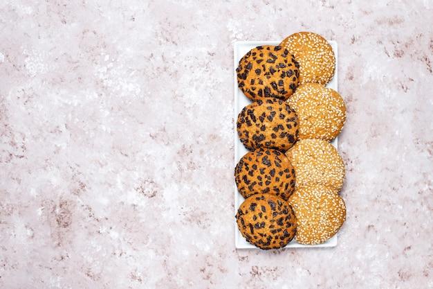 明るいコンクリート背景にさまざまなアメリカンスタイルのクッキーのセット。紙吹雪、ゴマ、ピーナッツバター、オートミール、チョコレートチップクッキーのショートブレッド。