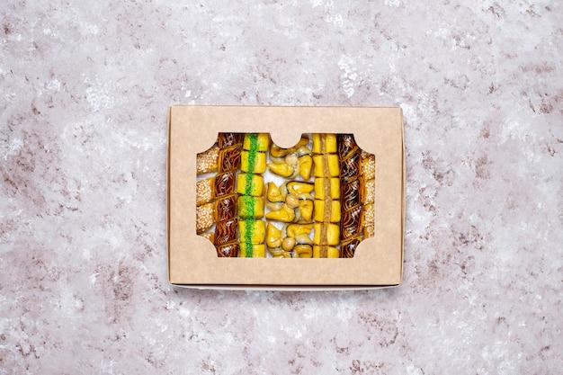 コンクリートの背景、平面図、コピースペースに異なるナッツを持つ伝統的な東洋のお菓子