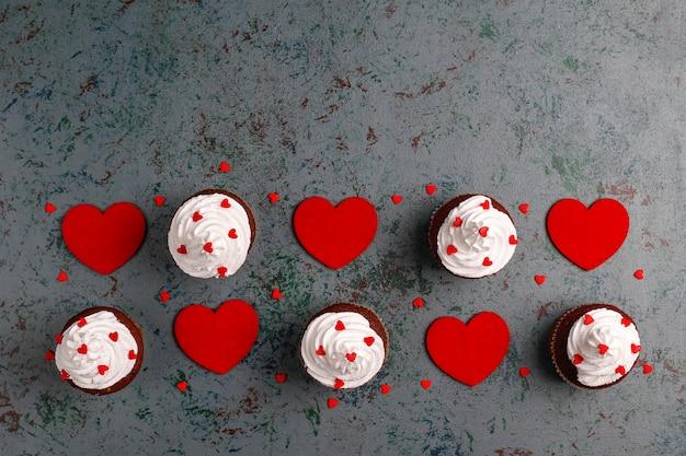 バレンタインデーの背景、ハート型のキャンディー、トップビューでチョコレートカップケーキ