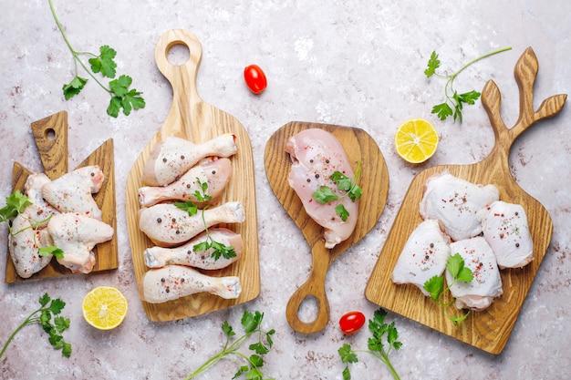 Сырое филе куриного мяса, бедра, крылья и ножки с травами, специями, лимоном и чесноком. вид сверху