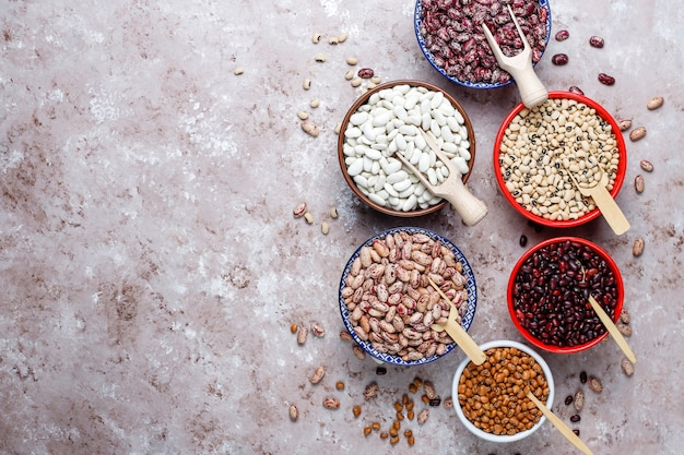 Бобовые и фасоль ассортимент в разные чаши на светлом фоне каменных. вид сверху. здоровая веганская протеиновая пища.