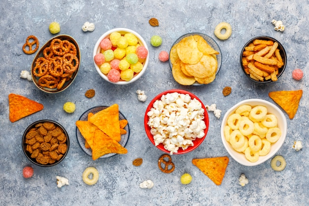 塩味のスナック。プレッツェル、チップ、クラッカー、ボウルにポップコーン。不健康な製品。図、皮膚、心臓、歯に悪い食品。高速炭水化物食品の品揃え