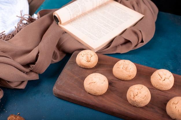 Сдобное печенье и кулинарная книга на разделочной доске