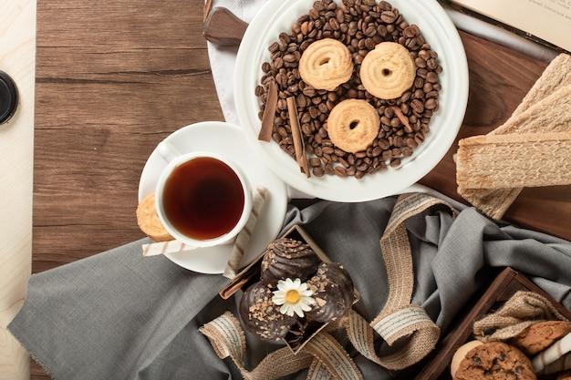 Печенье на кофейных зерен на блюдце и чашку чая. вид сверху