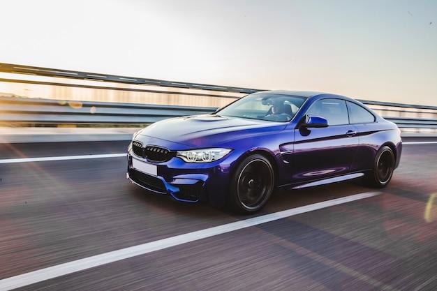 Синий седан скоростной езды по трассе