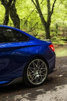 緑の木々、バックライト、ホイールの下のロマンチックな森をドライブする青いセダン