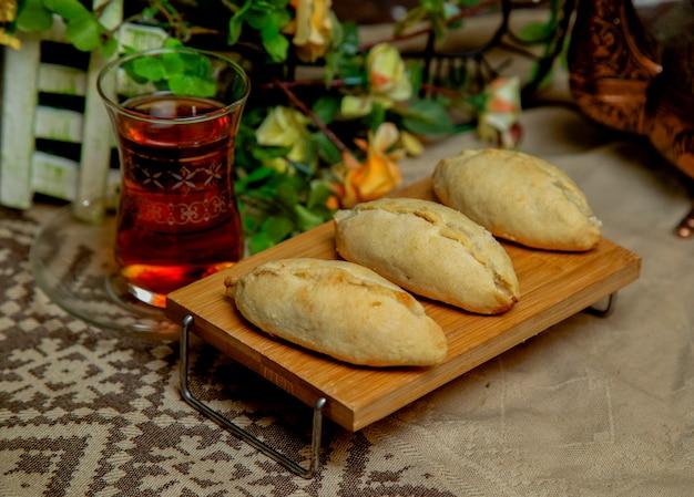 Традиционная восточная сладкая выпечка на маленьком деревянном столе, стакан чая и декоративная скатерть