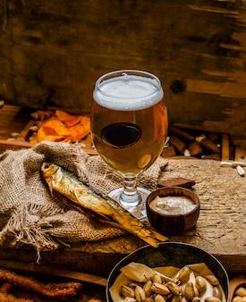 ラガービールジョッキ、ガラス、木製のテーブルの軽食。ナッツとドライフィッシュ - 画像