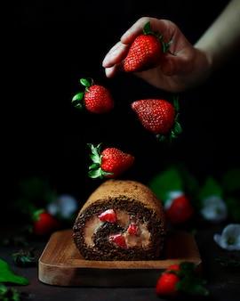 Шоколадно-клубничный сладкий рулет с парящей клубникой и женскими руками, темной едой