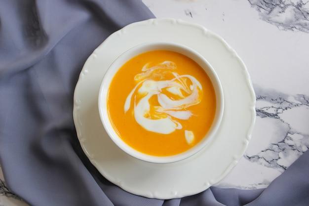 Две миски тыквенного супа на белом с серой тканью и кусочками тыквенного ореха