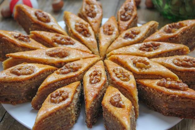 Традиционное азербайджанское праздничное печенье пахлава на белой тарелке на деревенском с орехами