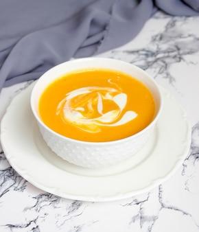 グレーの生地とバターナットスカッシュのスライスと白のカボチャスープ