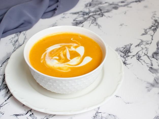 Миски тыквенного супа на белом фоне с серой тканью и кусочками тыквы