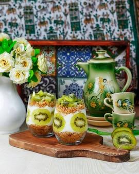 グラノーラとフレッシュカットキウイを背の高いグラスに入れたヘルシーヨーグルトデザート。