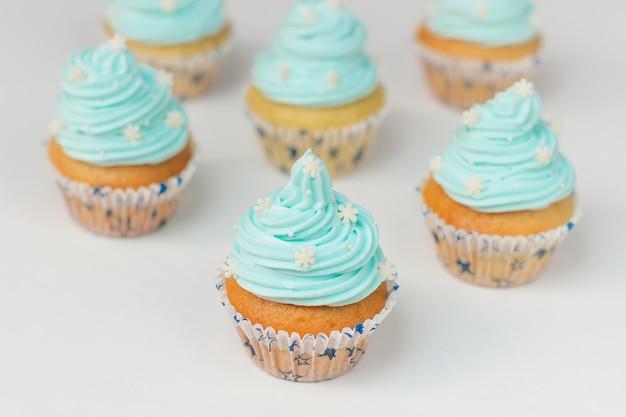 砂糖雪と青いクリームで飾られたカップケーキ。クリスマス冬のカップケーキ