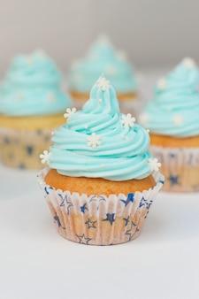 砂糖雪とブルークリームで飾られたカップケーキ。クリスマスカップケーキ
