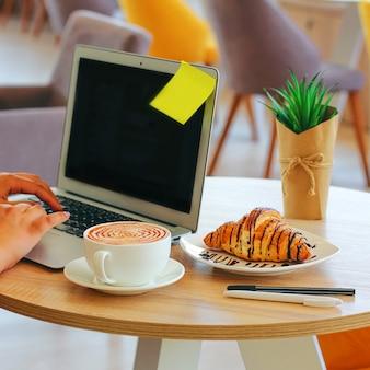 コーヒー、ラップトップ、クロワッサンは、朝、オフィスのテーブルでビジネス朝食を見せます。