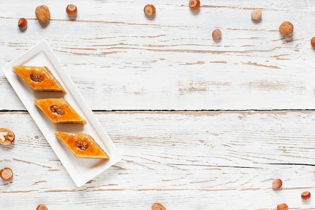 Традиционный азербайджанский праздник новруз печенье пахлава на белой тарелке на белом фоне с орехами и шакарбура