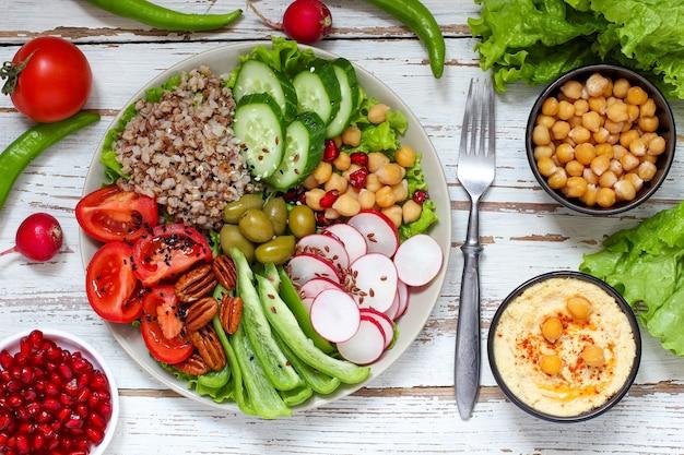 フムスのボウル、野菜スティック、ヒヨコ豆、オリーブ。
