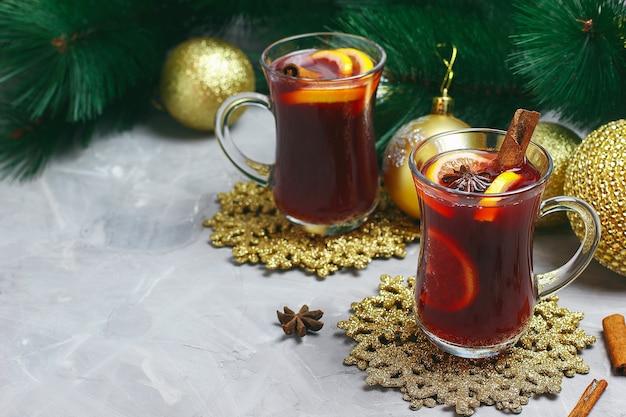 ゴールデンクリストマスの装飾が施された灰色のコンクリートにスパイスとレモンスライスのクリスマスホットワイン