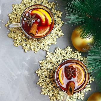 クリスマスゴールデンクリスマス装飾が施された灰色のコンクリートにスパイスとレモンスライスとホットワイン