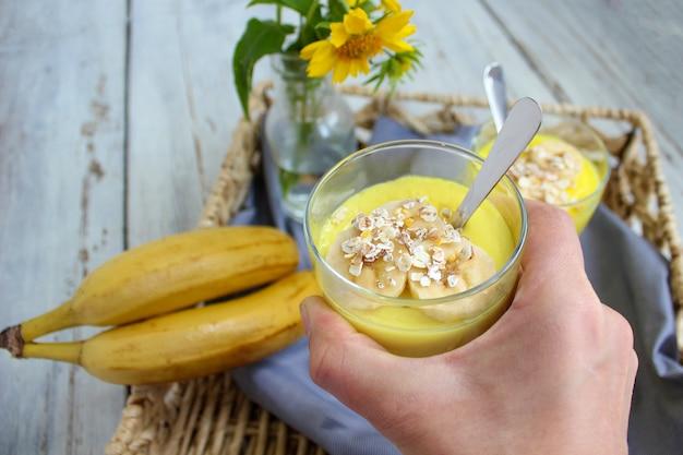 朝食のトレイにおいしいバナナプディンググラス