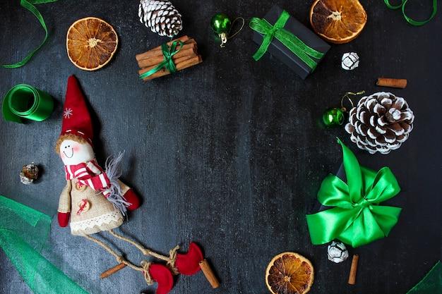 乾燥したオレンジ、白い松ぼっくり、緑のクリスマスツリーのボール、みかん、赤いリンゴ、ジンジャースティックとクリスマスの背景、