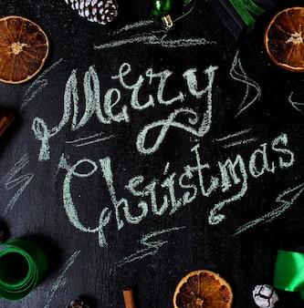 メリークリスマス、乾燥したオレンジ、白松ぼっくり、緑のクリスマスツリーのボールの言葉でクリスマスの背景
