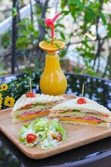 黒いガラステーブルにオレンジジュースのクラブサンドイッチ