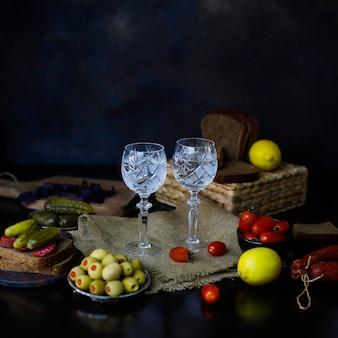 Водка с гарниром из лимона, маслин, хлеба