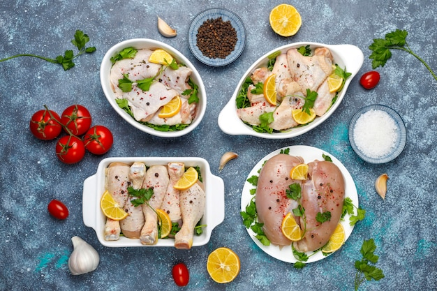 Сырое куриное мясо филе, бедра, крылья и ноги с травами, специями, лимоном и чесноком на синем фоне. вид сверху