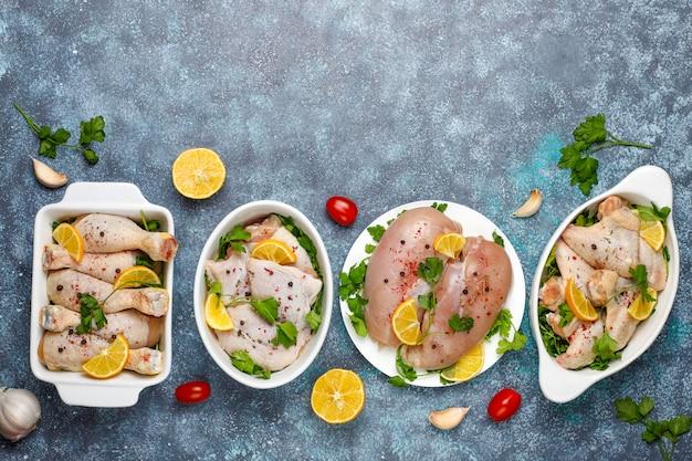 生鶏肉の切り身、太もも、翼、脚、ハーブ、スパイス、レモン、ニンニクと暗い青色の背景。上面図